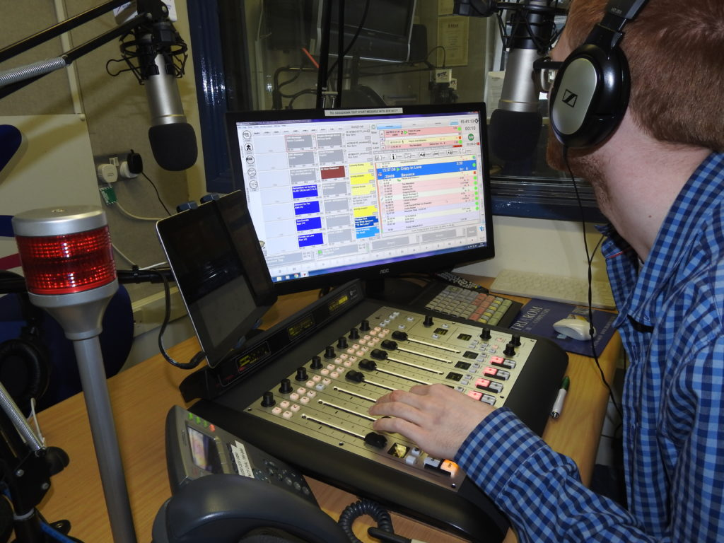 A Bay Trust Radio volunteer in the studio with a mixer, microphones and screens